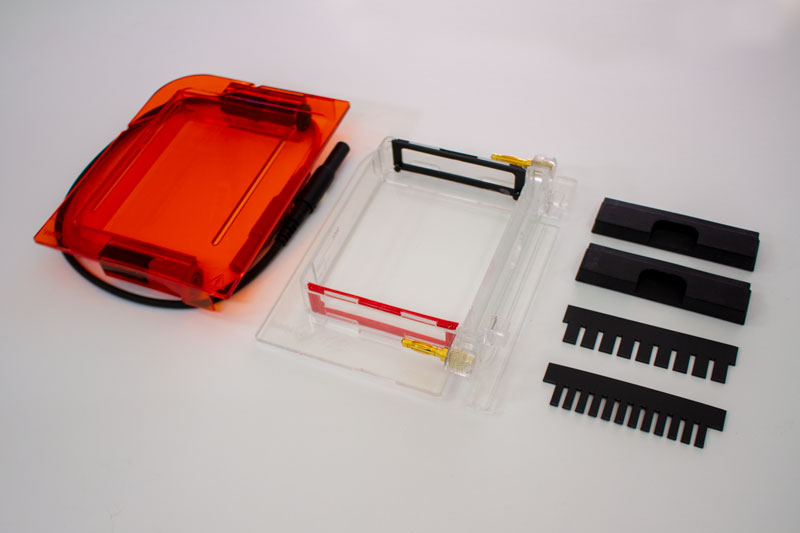Bento Lab Gel Electrophoresis Box - all parts laid out: Orange filter acrylic lid, clear acrylic tank with red and blue electrodes, two shutters, a 9 well and a 12 well comb.